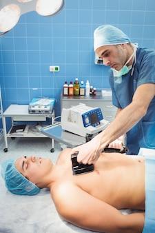 男性外科医が除細動器で無意識の患者を蘇生させる