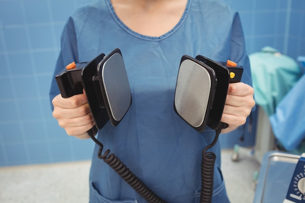 除細動器を保持している女性外科医の中間セクション