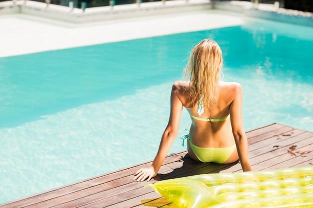 プールの端に座っている穏やかなブロンドの後姿