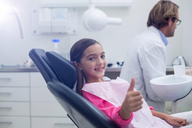 歯科医の椅子に座っている笑顔の若い患者