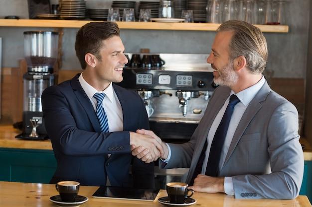 カフェで握手するビジネスマン