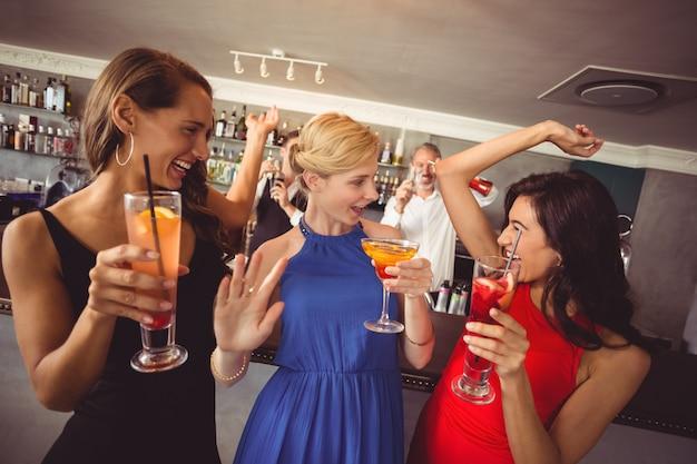 ダンスしながらカクテルのグラスを保持している女性の友人