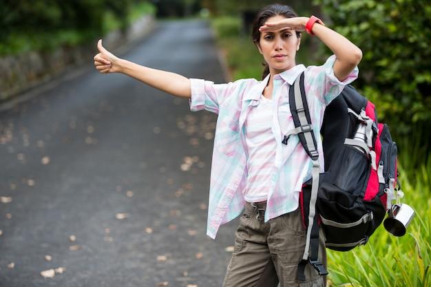 田舎道でヒッチハイクしている女性