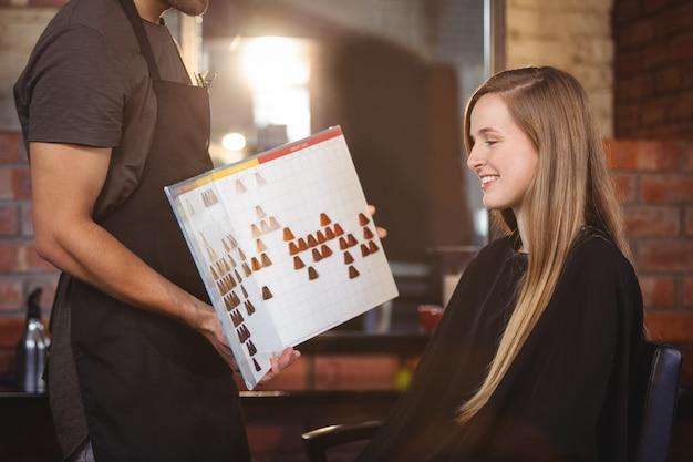 Женщина выбирает цвет волос со стилистом