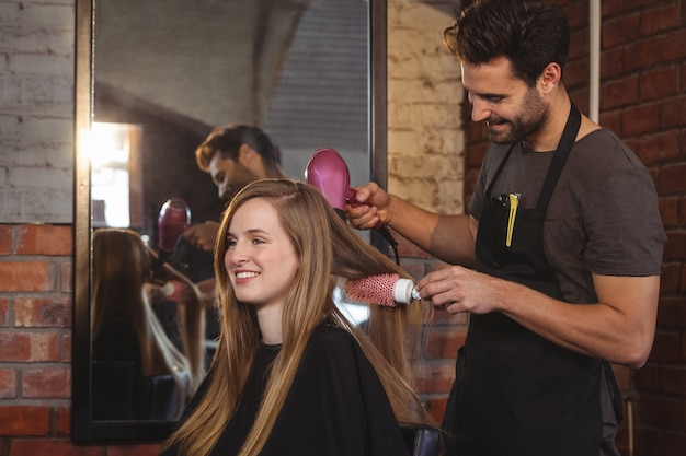 Милая женщина сушит волосы