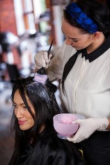 彼女のクライアントの髪を染める美容師