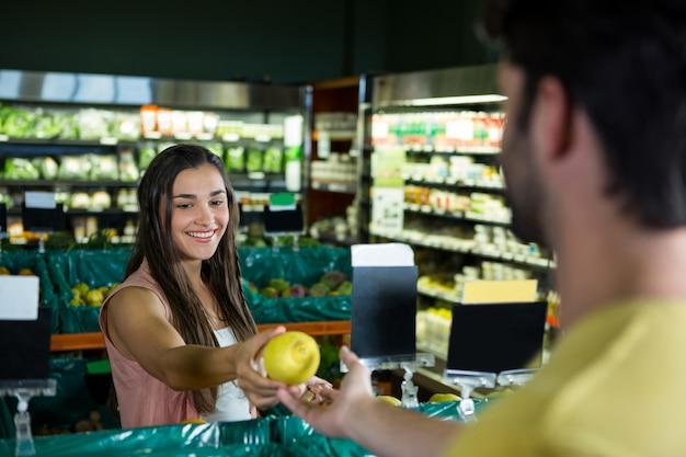 スーパーマーケットでの請求のためのレジ係に果物を与える女性