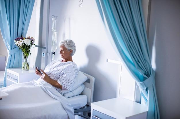 ベッドの上の携帯電話を使用して女性の上級の患者