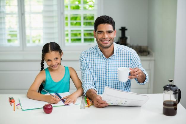 宿題をしている娘と家で新聞を読みながら紅茶のカップを持つ父親