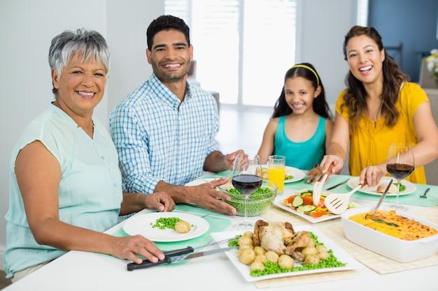 Счастливая семья много поколений имея еду на таблице дома