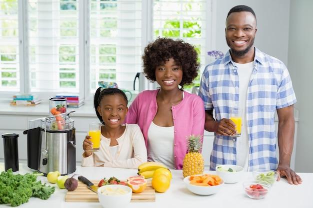 笑顔の両親とキッチンでオレンジジュースのガラスを持つ娘