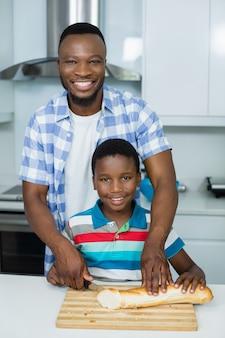 父が自宅のキッチンでパンをカットする息子を支援