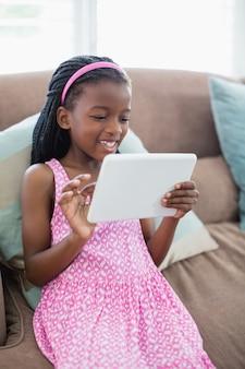 Девушка сидит на диване и с помощью цифрового планшета в гостиной