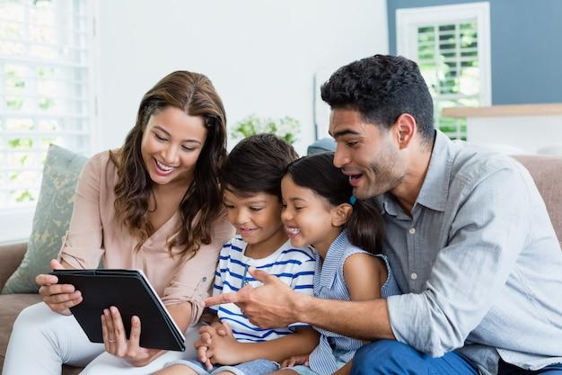 親と子供がリビングルームでデジタルタブレットを使用して