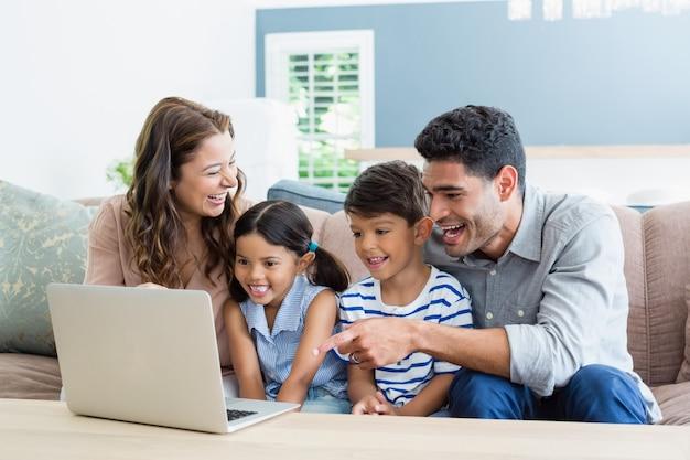 親と子供が居間でノートパソコンを使用して
