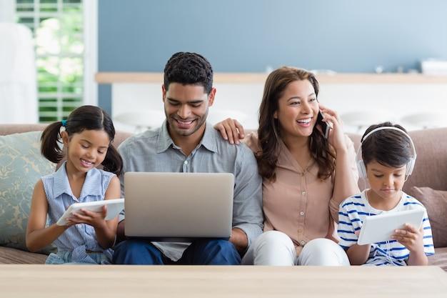 Родители и дети, используя ноутбук и цифровой планшет в гостиной