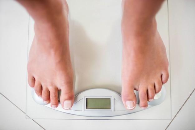 自宅での体重計上の女性の足