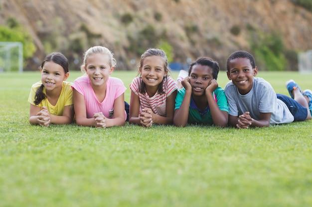 遊び場で横になっている学校の子供たち