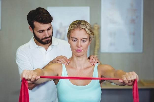 Мужской физиотерапевт дает массаж плеч пациентке