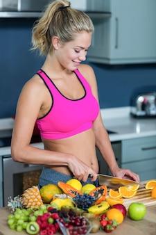 台所で女性カットフルーツを合わせる