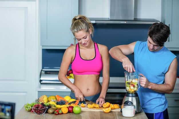 健康的なカップルが台所でスムージーを準備します。
