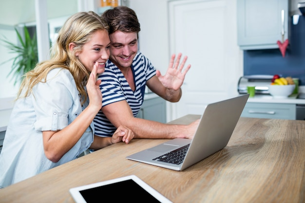 台所でラップトップを使用して幸せなカップル