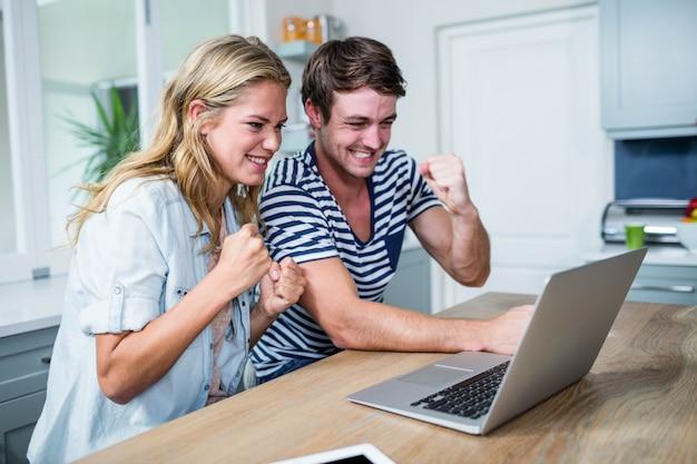台所でラップトップ上のビデオを見て幸せなカップル