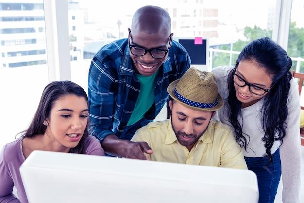Взгляд высокого угла счастливых бизнесменов обсуждая на столе в творческом офисе