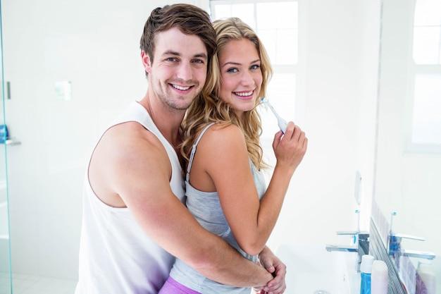 若いカップルが自宅の浴室で彼らの歯を磨く
