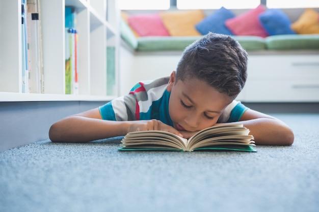 床に横たわって、図書館で本を読んでいる少年