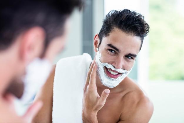 ハンサムな男の浴室で彼のひげを剃る