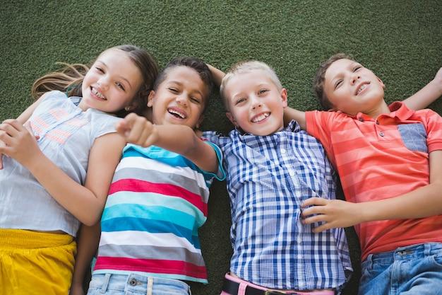 キャンパスの草の上に横たわる笑顔の学童