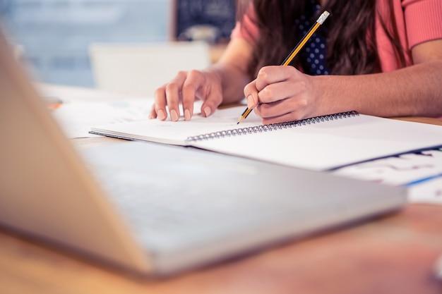 創造的なオフィスの机の上の本を書くの実業家
