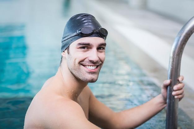 ハンサムな男がプールで水から抜け出す