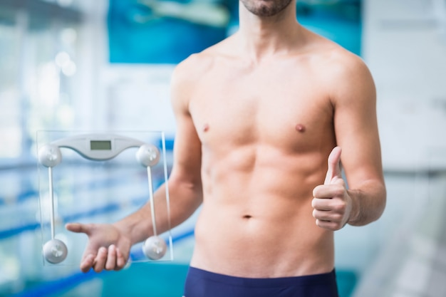 プールで親指で体重計を持ってフィット男