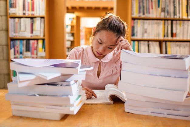 Напряженная молодая женщина учится в библиотеке