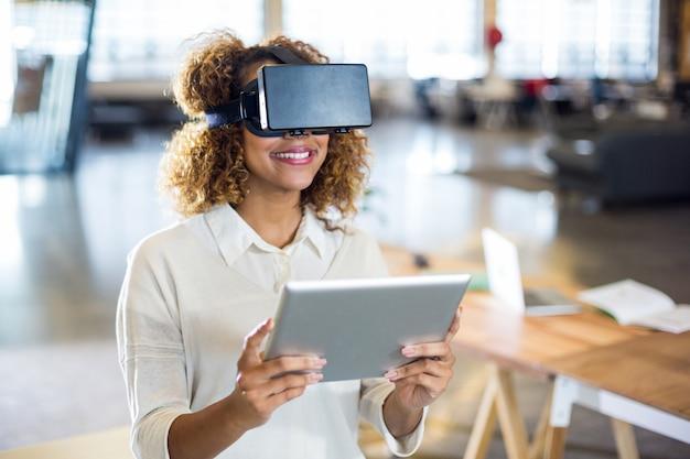 Стекло виртуальной реальности женщины нося с цифровой таблеткой