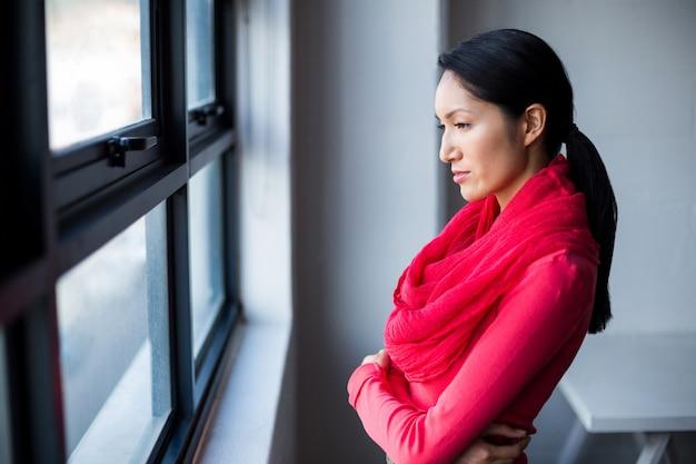 オフィスの窓際に立っている思いやりのある女性