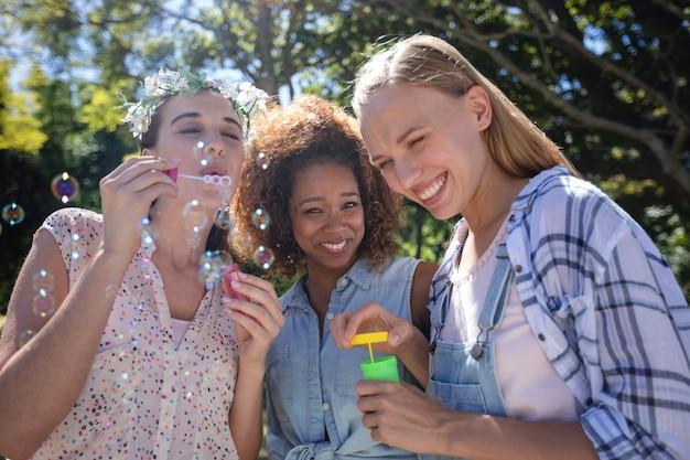 Подруги дуют пузырь в парке