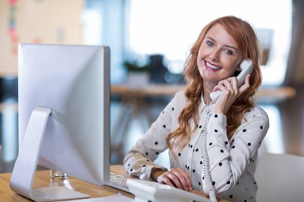 Творческая деловая женщина разговаривает по телефону