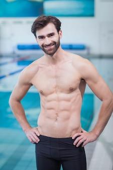 Красивый мужчина без рубашки, стоя с руки на бедрах в бассейне
