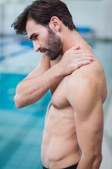 プールで肩の痛みを持つハンサムな男