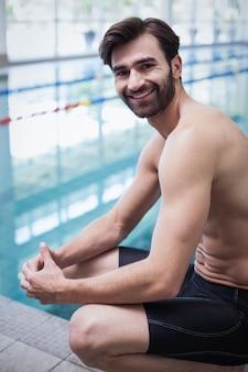 Улыбающийся человек сидит на краю воды у бассейна