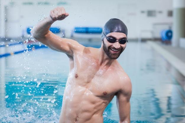 Улыбающийся человек торжествует с поднятой рукой в бассейне