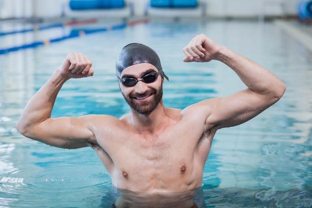 Улыбающийся человек торжествует с поднятыми руками в бассейне