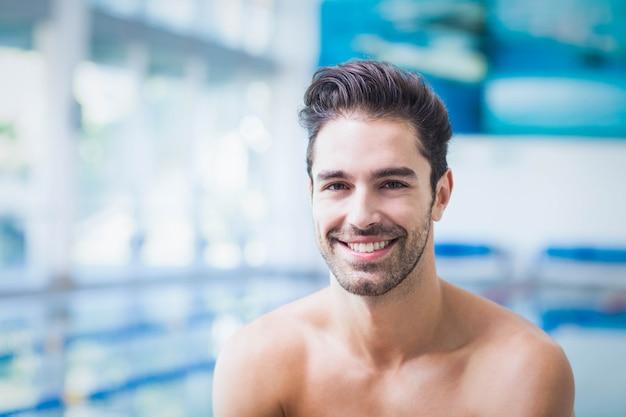 笑みを浮かべて男がプールでカメラを見て