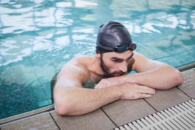 プールの端に休んで疲れた男