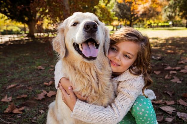 Маленькая девочка обнимает свою собаку
