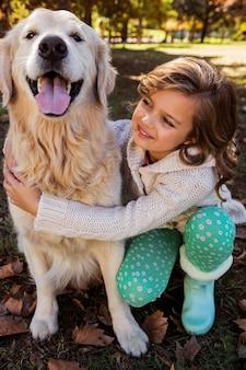 Портрет маленькой девочки обнимая ее собаку