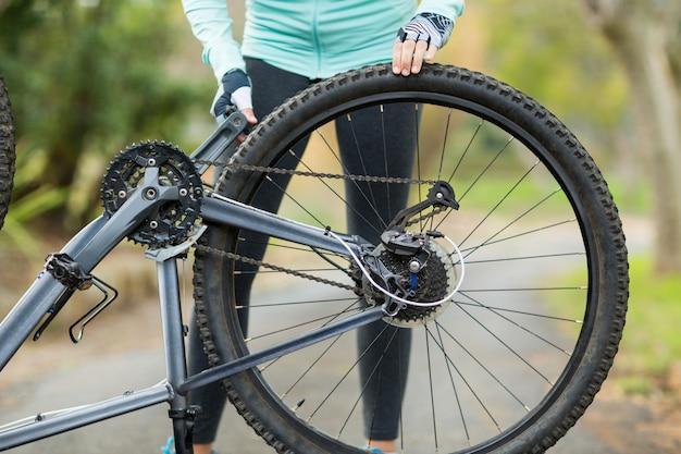 自転車のタイヤを修理する女性の中央部